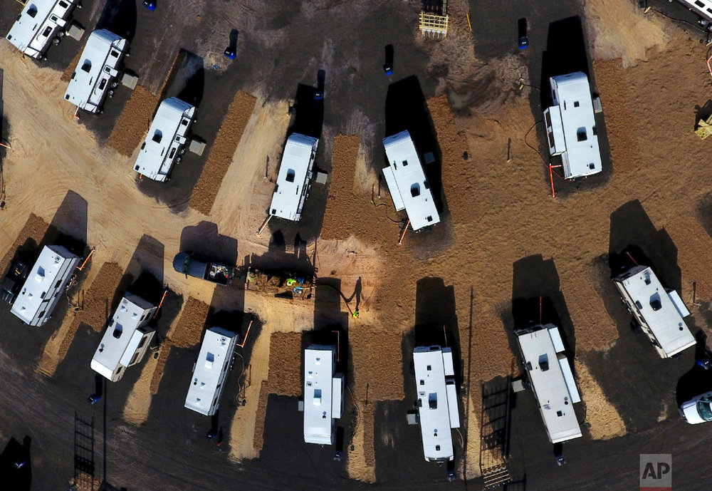 A worker sprays straw around newly setup Federal Emergency Management Agency trailers for residents left homeless by Hurricane Michael in Panama City, Fla, Thursday, Jan. 24, 2019. (AP Photo/David Goldman)