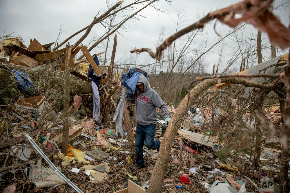 Danny Allen helps recover belongings while sifting through the debris of a friend's home destroyed by a tornado in Beauregard, Ala., March 4, 2019. (AP Photo/David Goldman)