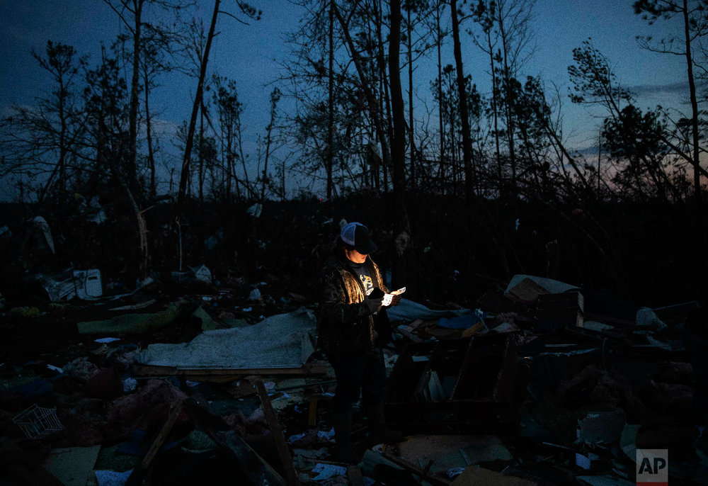 Matthew Schell looks for personal mementos by flashlight at dusk in the rubble of the house destroyed by a tornado which killed his uncle, David Wayne Dean, in Beauregard, Ala., March 4, 2019. (AP Photo/David Goldman)