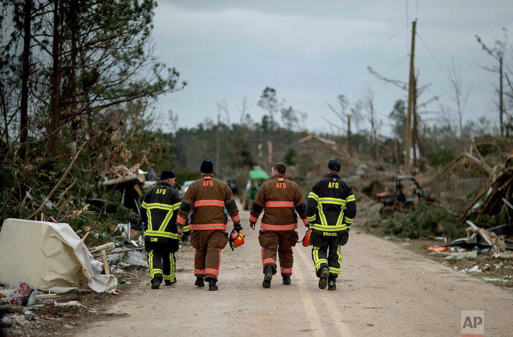 First responders walk through a neighborhood heavily damaged by a tornado a day earlier in Beauregard, Ala., March 4, 2019. (AP Photo/David Goldman)