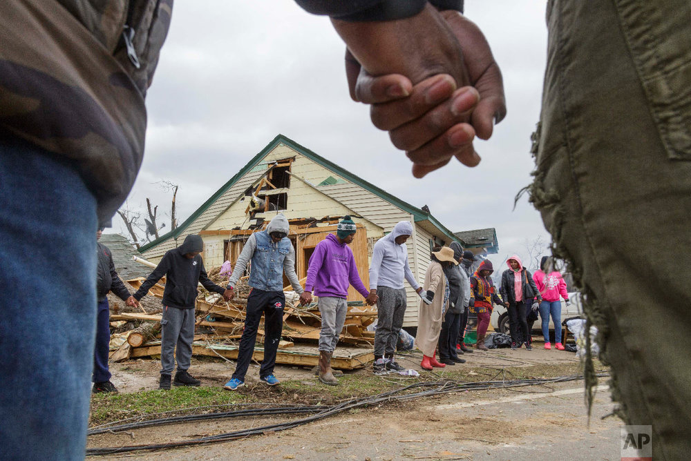 Residents of Talbotton, Ga., pray together outside a home destroyed by a tornado the day after storms battered Alabama and Georgia, March 4, 2019. (Grant Blankenship/The Macon Telegraph via AP)