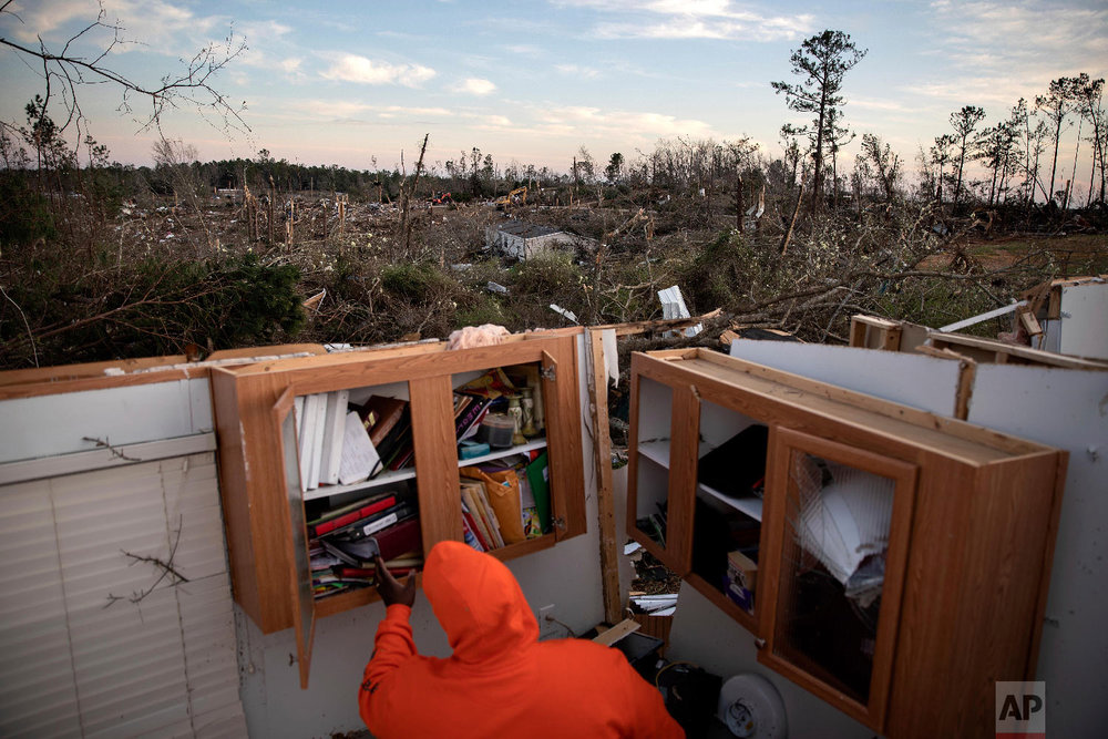 Granadas Baker retrieves personal items from his home after a tornado caused extensive damage to a neighborhood a day earlier in Beauregard, Ala., March 4, 2019. (AP Photo/David Goldman)