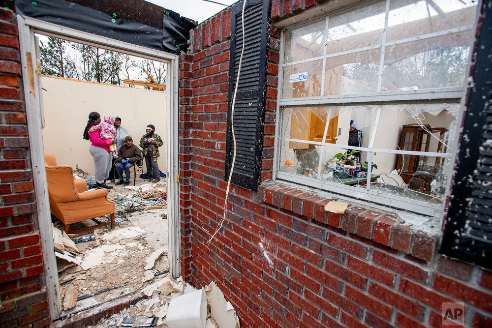Dorothy Wilborn, seated, is comforted by her family in her home near Beauregard, Ala., on March 4, 2019, that lost it's roof in the fatal tornado that struck the area on Sunday afternoon. (Mickey Welsh/The Montgomery Advertiser via AP)