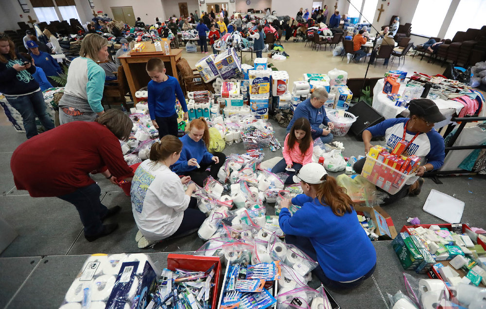 Dozens of volunteers help sort donated supplies pouring in from the community and local businesses at the Providence Baptist Church for those affected in nearby Beauregard a day after a tornado, March 4, 2019, in Opelika, Ala. (Curtis Compton/Atlanta Journal-Constitution via AP)