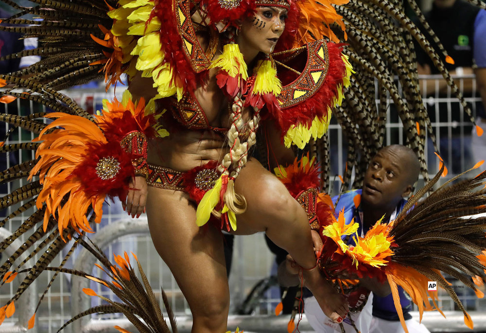 A dancer from the Academicos do Tucuruvi samba school is assisted by a fellow dancer as she performs during a carnival parade in Sao Paulo, Brazil, Saturday, March 2, 2019. (AP Photo/Andre Penner)