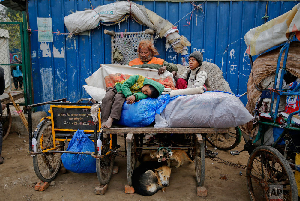 7-year-old Farmaan falls asleep on a pile of their belongings placed on a wooden fruit vendor's cart, which they call their home, in New Delhi, India on Feb. 1, 2019. (AP Photo/Altaf Qadri)