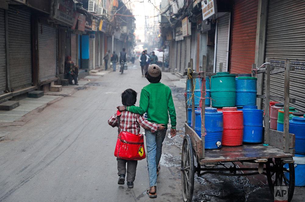 13-year-old Ajmeri, right, walks his younger brother Farmaan to school in New Delhi, India, on Jan. 18, 2019. (AP Photo/Altaf Qadri)