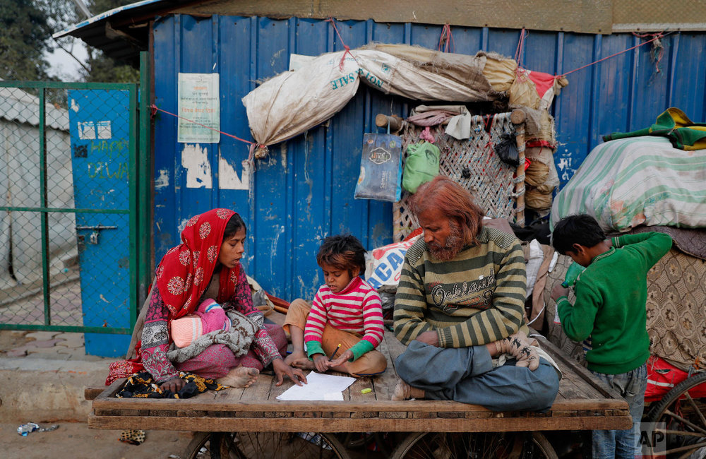 Ruby Khan, left, and Nisar Khan help their 7-year-old son Farmaan with his homework as they sit on a wooden fruit vendor's cart, which is their home, in New Delhi, India, on Jan. 16, 2019. (AP Photo/Altaf Qadri)