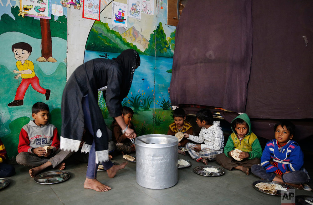 7-year-old Farmaan, second from right, waits to be served lunch meals at Salaam Baalak Trust, an NGO working for street children, in New Delhi, India on Jan. 31, 2019. (AP Photo/Altaf Qadri)