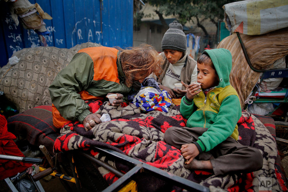 7-year-old Farmaan, right, drinks tea as his father Nasir Khan and his mother Ruby Khan tend to their three-month-old daughter Razia, while they sit on a wooden fruit vendor's cart which is their home in New Delhi, India, on Feb. 1, 2019. (AP Photo/Altaf Qadri)
