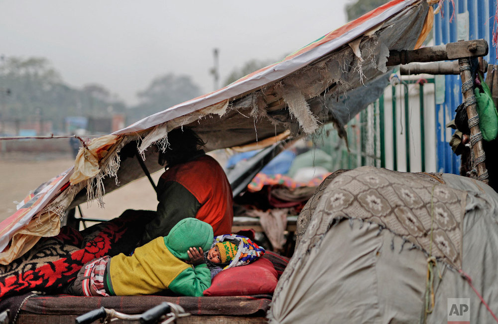 7-year-old Farmaan, back to camera, lies next to his three-month-old sister Razia on a wooden fruit vendor's cart, which is his home, as they wake up on a cold morning in New Delhi, India on Feb. 1, 2019. (AP Photo/Altaf Qadri)