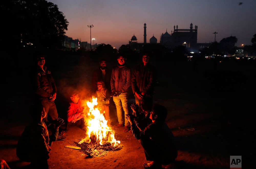 7-year-old Farmaan, fourth from left, and other homeless and daily wage laborers keep themselves warm around a bonfire in New Delhi, India on Jan. 18, 2019. (AP Photo/Altaf Qadri)