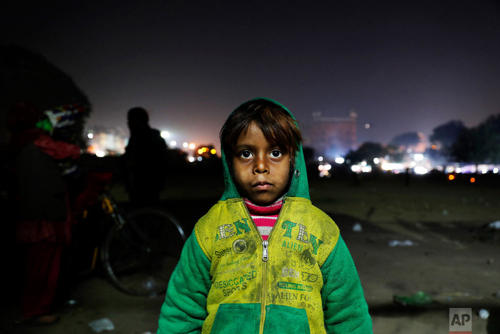 7-year-old Farmaan poses for a photograph near his home, a wooden fruit vendor's cart, in New Delhi, India on Jan. 18, 2019. (AP Photo/Altaf Qadri)
