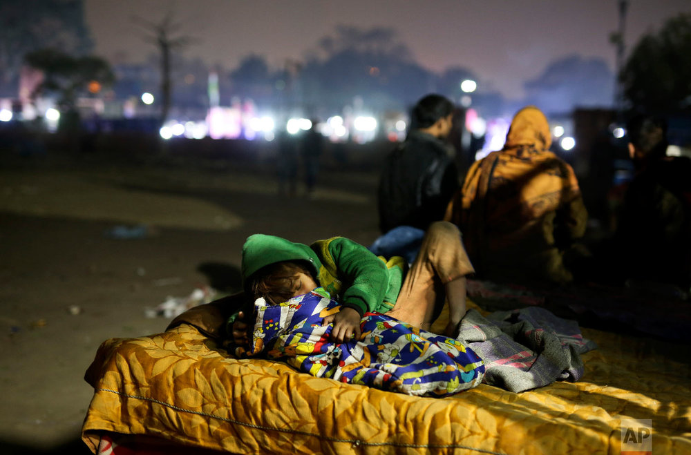 7-year-old Farmaan falls asleep while attending to his 3-month-old sister Razia, on a hand cart, which is their family's home, in New Delhi, India on Jan. 18, 2019. (AP Photo/Altaf Qadri)