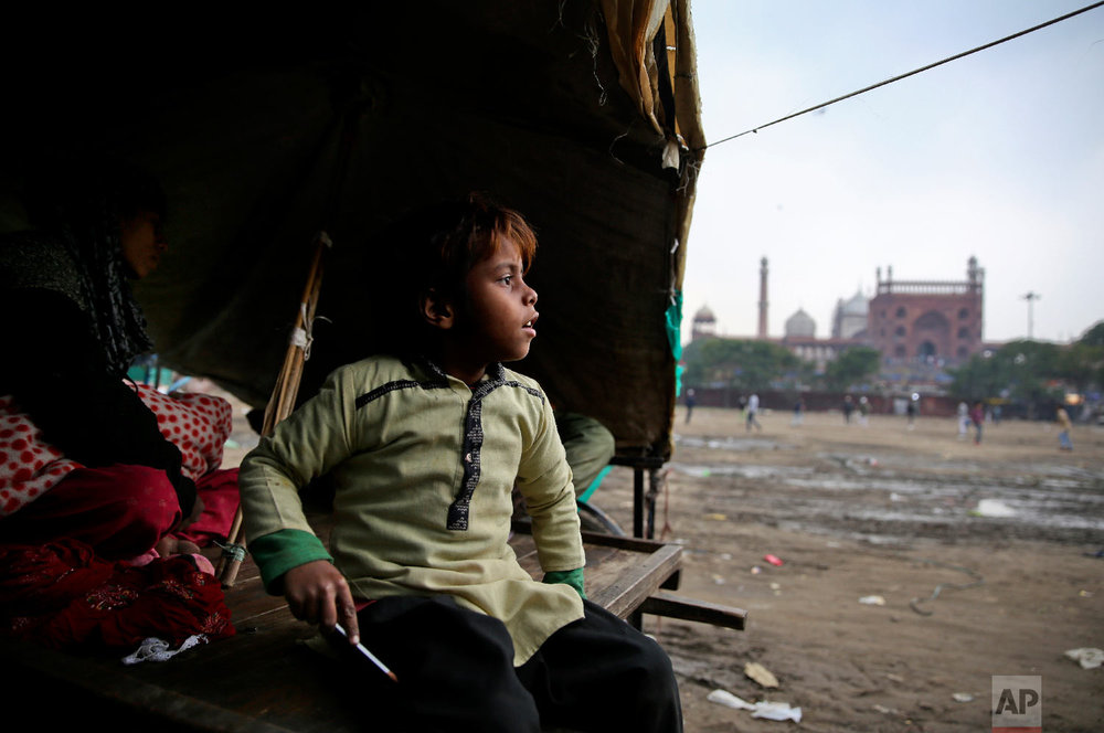 7-year-old Farmaan looks out from his home, set up on a wooden fruit vendor's cart, as it drizzles in New Delhi, India on Jan. 24, 2019, photo. (AP Photo/Altaf Qadri)