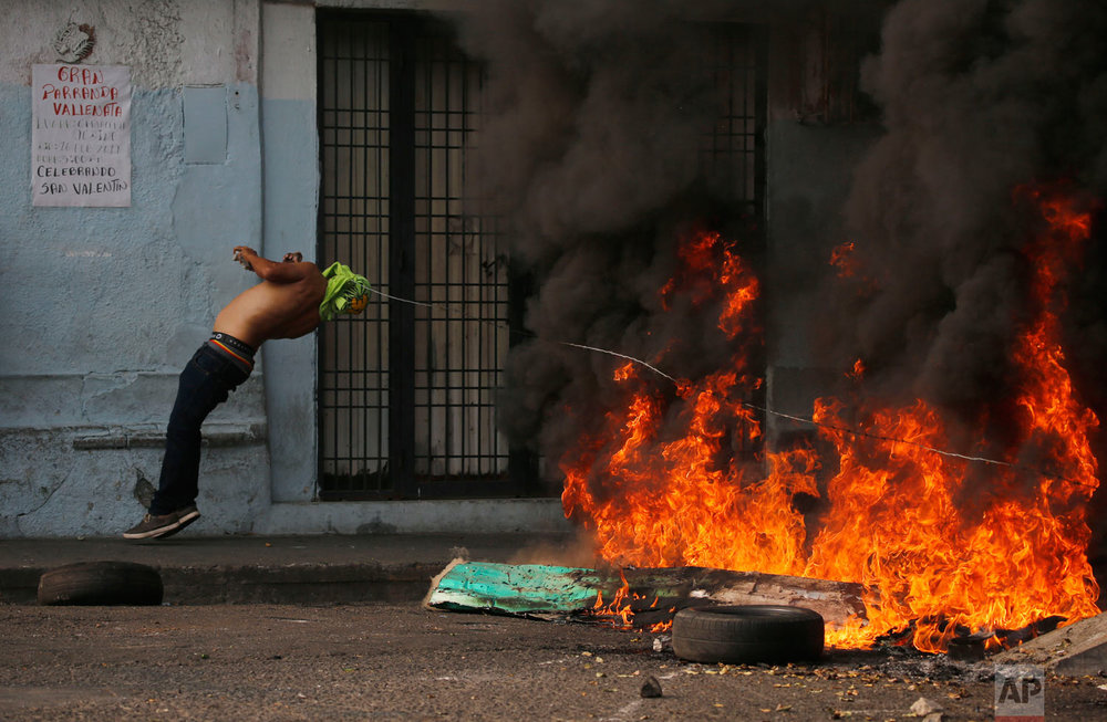 A demonstrator gets caught in a strand of barbed wire during clashes with the Bolivarian National Guard in Urena, Venezuela, near the border with Colombia,  Feb. 23, 2019.  (AP Photo/Fernando Llano)