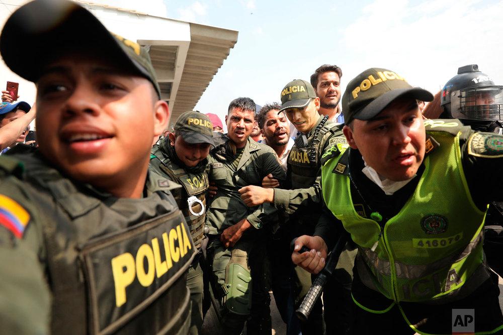 Colombian police escort a Venezuelan soldier who deserted his post at the Simon Bolivar International Bridge, where Venezuelans tried to deliver humanitarian aid despite objections from President Nicolas Maduro, in Cucuta, Colombia, Feb. 23, 2019. (AP Photo/Fernando Vergara)