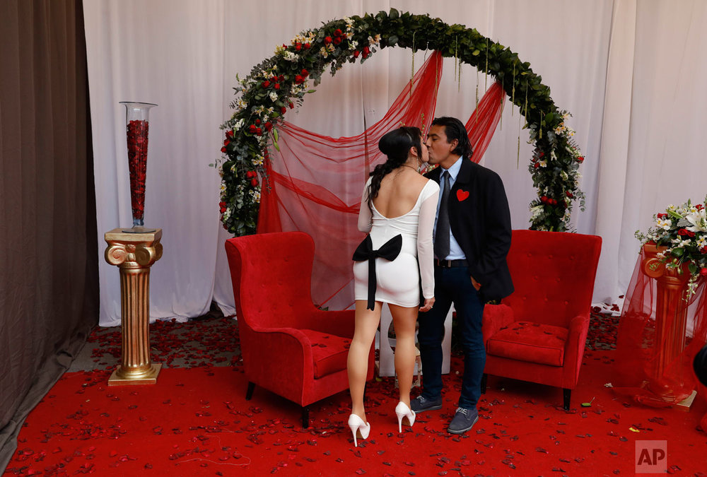 A bride and groom kiss while posing for photos at one of several free sets placed for newlyweds  to take cell phone photos of themselves, following a mass wedding ceremony on Valentine's Day in Mexico City, Feb. 14, 2019. (AP Photo/Rebecca Blackwell)