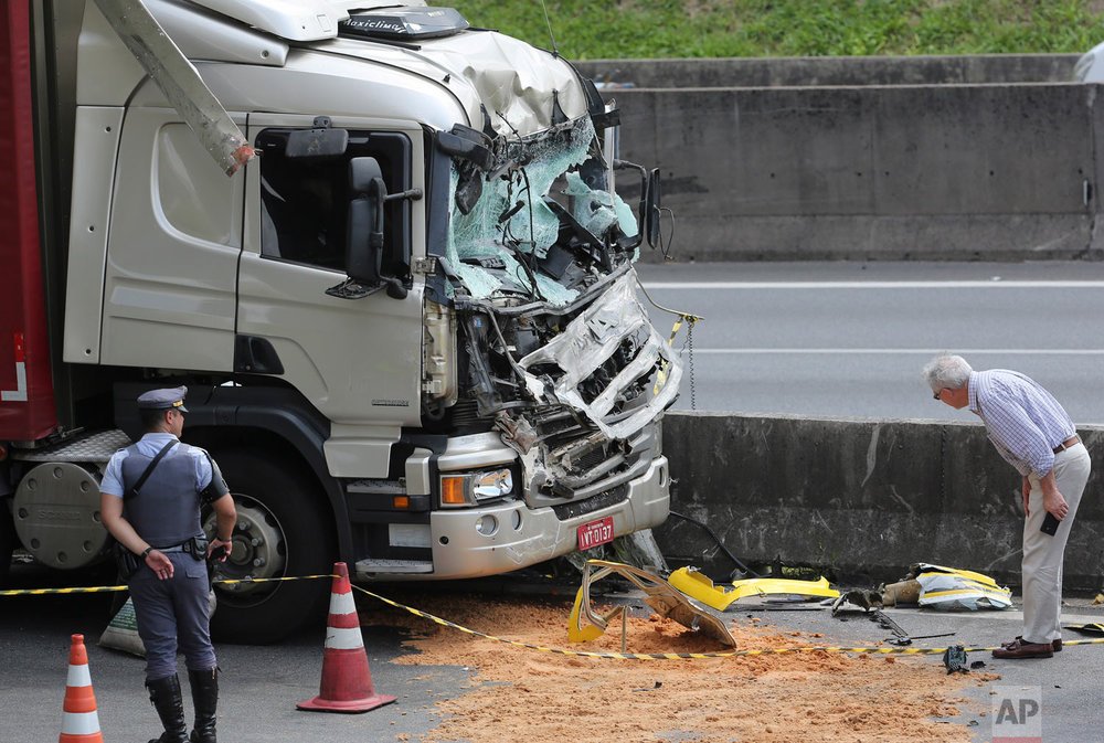 A man looks at wreckage from a helicopter where it crashed into the front of a cargo truck during an emergency landing, on a main highway in Sao Paulo, Brazil, Feb. 11, 2019. 66-year-old Brazilian television news anchor Ricardo Boechat and the pilot perished in the accident. (AP Photo/Andre Penner)