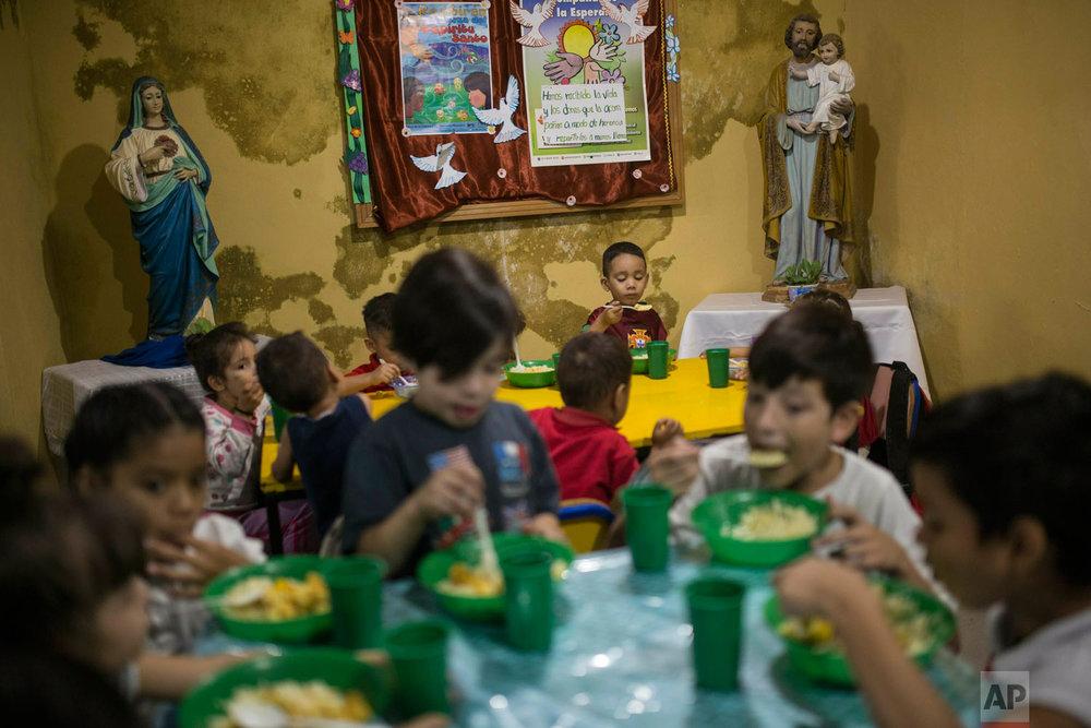 Children have lunch in San Antonio de Padua soup kitchen in the Petare slum, in Caracas, Venezuela, Feb. 11, 2019. (AP Photo/Rodrigo Abd)
