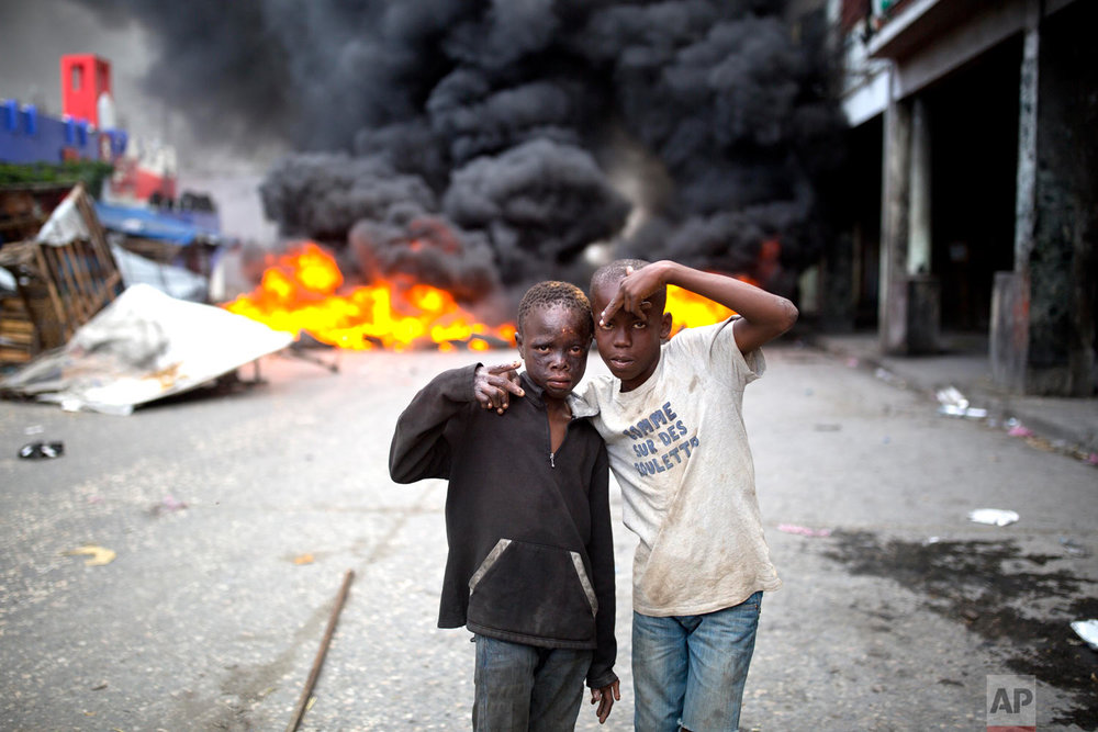 Homeless boys strike a pose in front of a road block set ablaze by protesters demanding the resignation of President Jovenel Moise in Port-au-Prince, Haiti, Feb. 10, 2019. (AP Photo/Dieu Nalio Chery)