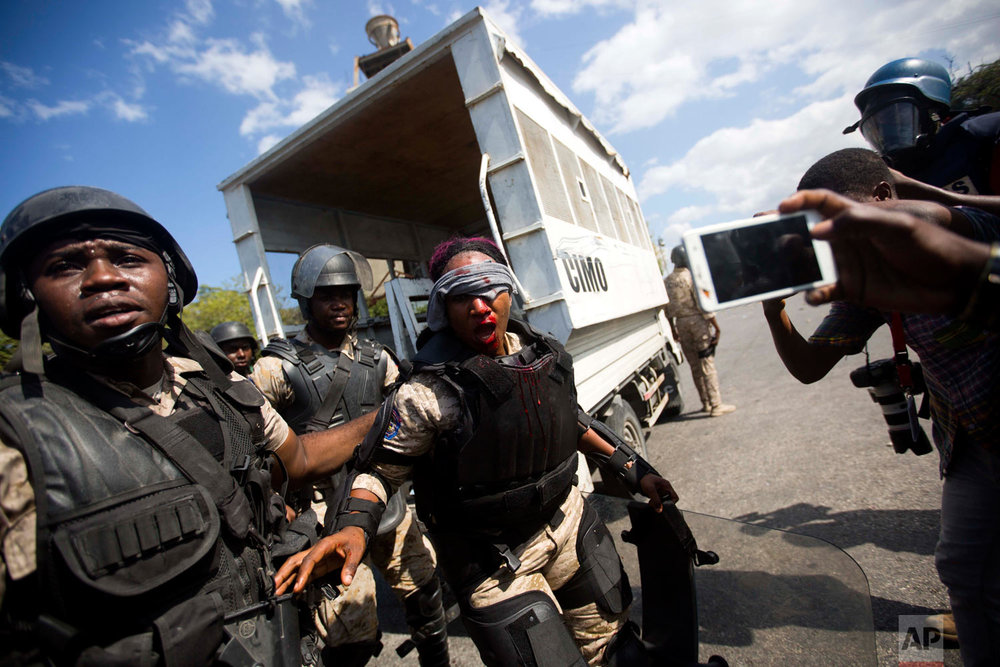 A national police officer is helped by fellow officers after she was injured in the face from a rock thrown by protesters demanding the resignation of Haitian President Jovenel Moise, near the presidential palace in Port-au-Prince, Haiti, Feb. 13, 2019. (AP Photo/Dieu Nalio Chery)