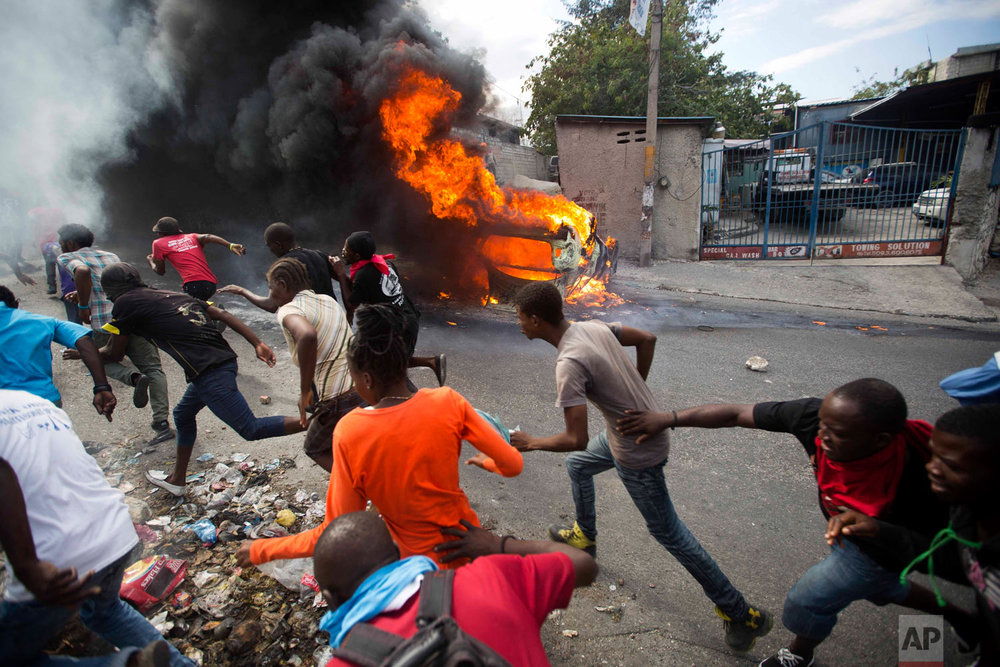 Demonstrators run from police who are shooting in their direction, as a car burns during a protest demanding the resignation of Haitian President Jovenel Moise in Port-au-Prince, Haiti, Feb. 12, 2019. (AP Photo/Dieu Nalio Chery)