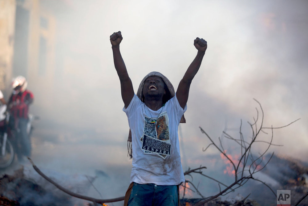 A demonstrator stands in the street chanting slogans against President Jovenel Moise during a protest to demand his resignation, in Port-au-Prince, Haiti, Feb. 9, 2019. (AP Photo/Dieu Nalio Chery)