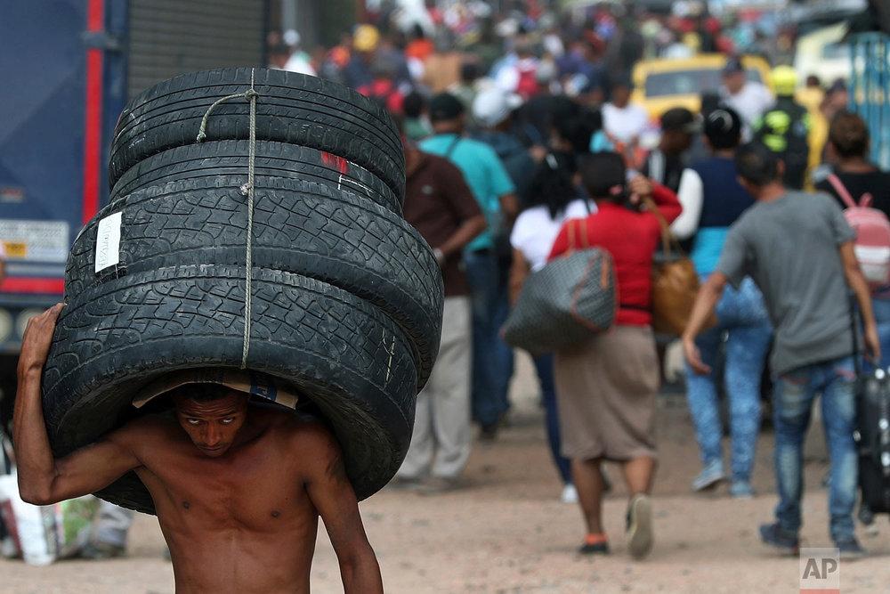 A man hauls used tires back to Venezuela, using a blind spot on the border near the closed Simon Bolivar International Bridge, in La Parada, Colombia, Feb. 28, 2019. (AP Photo/Martin Mejia)