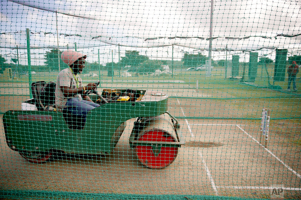 A groundskeeper rolls the pitch at the nets prior to a training session of the England cricket team at the Sir Vivian Richards stadium in North Sound, Antigua and Barbuda, Feb. 4, 2019. (AP Photo/Ricardo Mazalan)