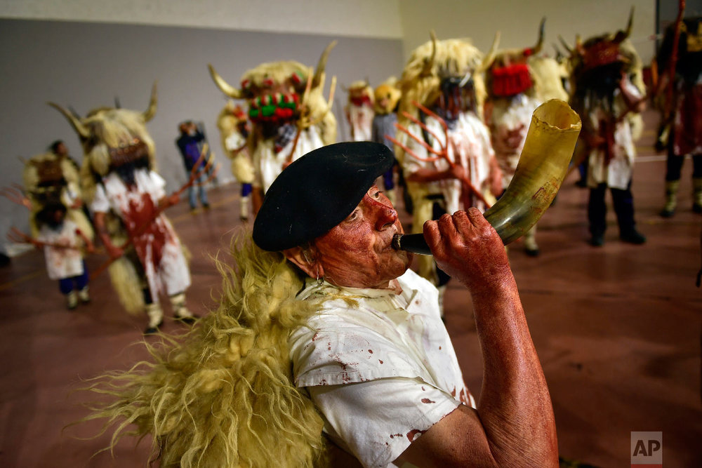 """A man plays a horn as """"momotxorros """" take part in the carnival wearing typical carnival dress, in Alsasua, northern Spain, Tuesday, March 5, 2019. (AP Photo/Alvaro Barrientos)"""