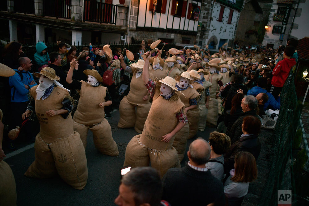 """People dressed as the traditional carnival characters """"Zaku Zaharrak,"""" or old sack, in Basque language, take part during carnival parade in the small Pyrenean village of Lesaka, northern Spain, Sunday, March 3, 2019. (AP Photo/Alvaro Barrientos)"""