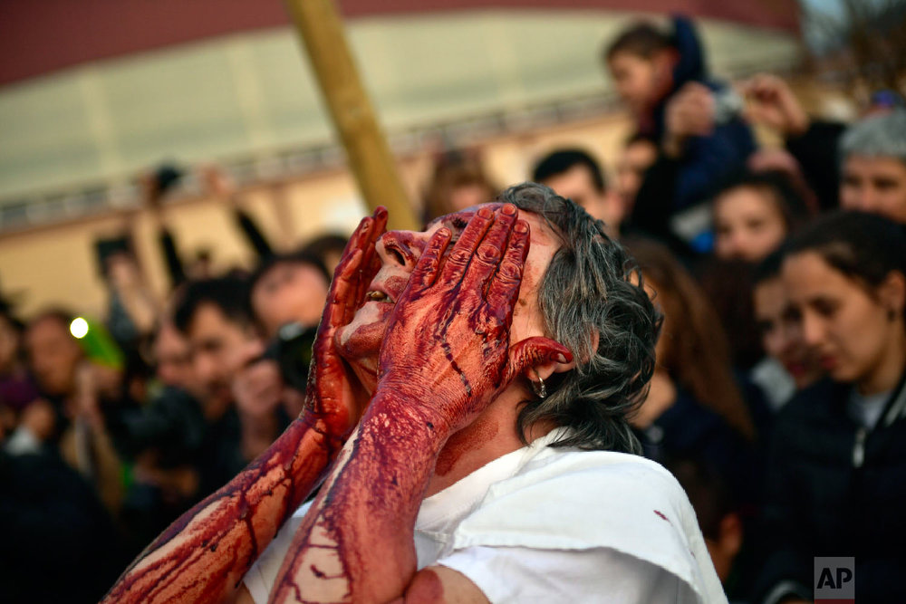 """A """"momotxorro'' covers his face with blood while taking part in the carnival wearing typical carnival dress, in Alsasua, northern Spain, Tuesday, March 5, 2019. (AP Photo/Alvaro Barrientos)"""