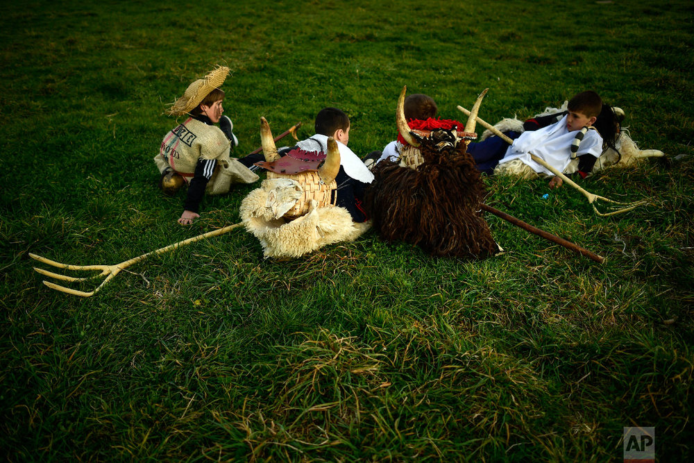 """Young """"momotxorros """" rest on the ground before taking part in the carnival wearing typical carnival dress, in Alsasua, northern Spain, Tuesday, March 5, 2019. (AP Photo/Alvaro Barrientos)"""