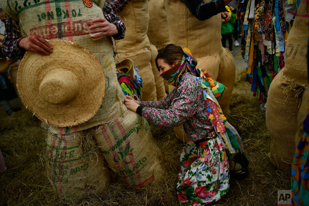 """People dressed as the traditional carnival characters """"Zaku Zaharrak,"""" or old sack, in Basque language, prepare to take part in the carnival parade in the small Pyrenean village of Lesaka, northern Spain, Sunday, March 3, 2019. (AP Photo/Alvaro Barrientos)"""