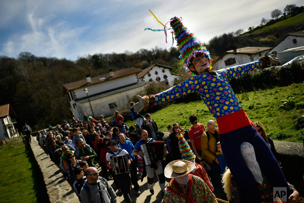 """People carry a giant """"Miel Otxin'', the symbol of the carnival, during an ancient rural carnival in the small Pyrenees village of Lantz, northern Spain, Sunday, March 3, 2019. (AP Photo/Alvaro Barrientos)"""