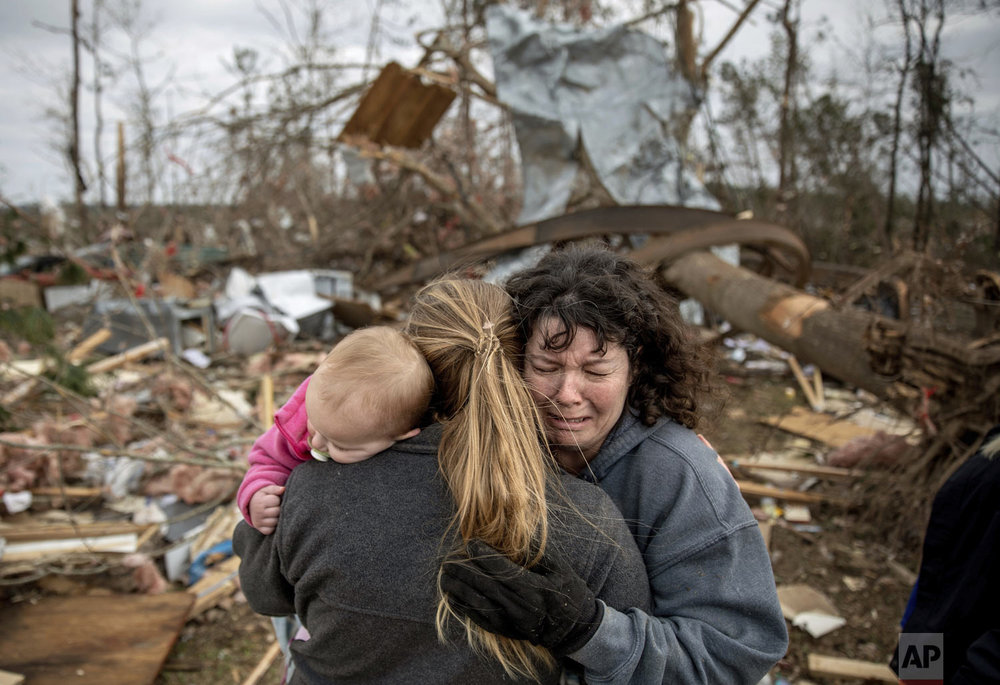 "Carol Dean, right, cries while embraced by Megan Anderson and her 18-month-old daughter Madilyn, as Dean sifts through the debris of the home she shared with her husband, David Wayne Dean, who died when a tornado destroyed the house in Beauregard, Ala., Monday, March 4, 2019. ""He was my wedding gift,"" said Dean of her husband whom she married three years ago. ""He was one in a million. He'd send me flowers to work just to let me know he loved me. He'd send me some of the biggest strawberries in the world. I'm not going to be the same."" (AP Photo/David Goldman)"