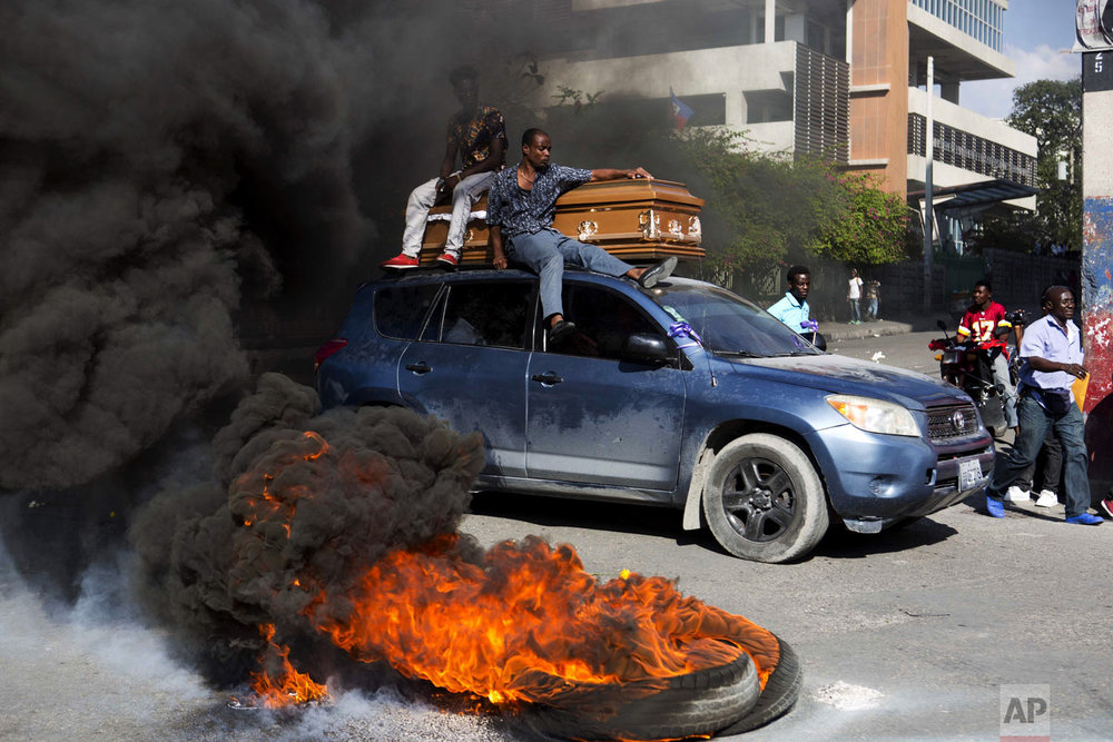 A car transports a coffin containing the body of one of the demonstrators who was killed during previous protests in Port-au-Prince, Haiti, Monday, March 4, 2019. People are protesting skyrocketing inflation and the government's failure to prosecute embezzlement from a multi-billion Venezuelan program that sent discounted oil to Haiti. (AP Photo/Dieu Nalio Chery)