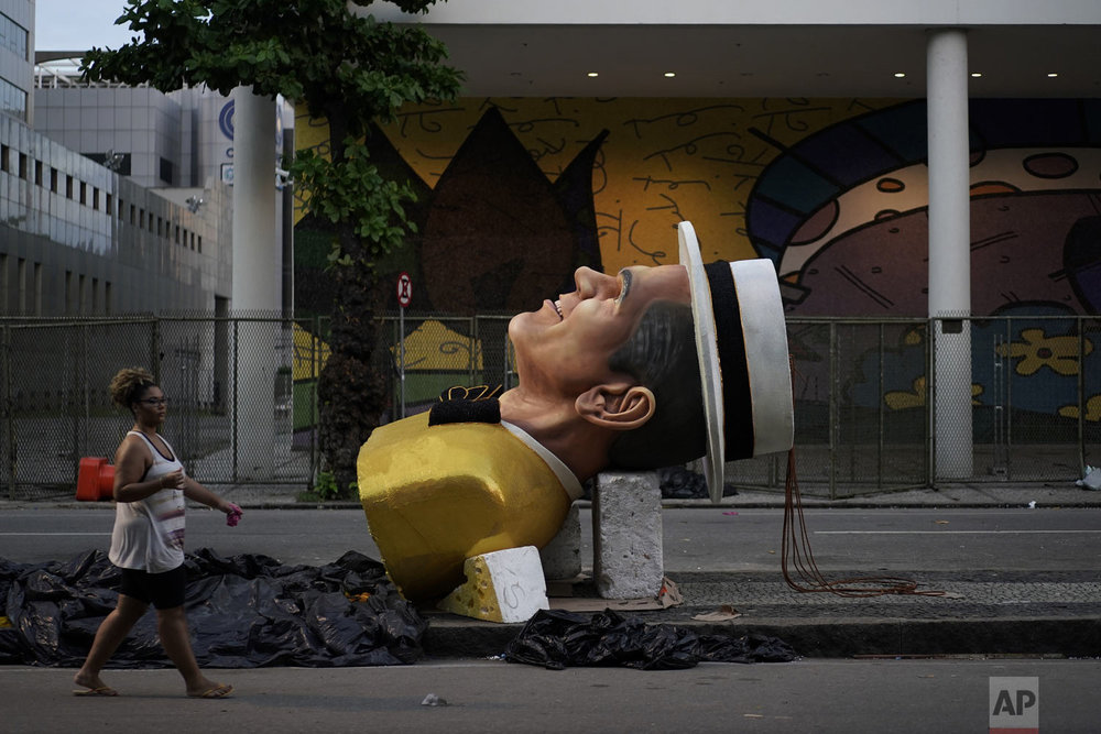 A woman walks past a sculpture, part of a float yet to be installed, for the Carnival parade at the Sambadrome in Rio de Janeiro, Brazil, Monday, March 4, 2019. (AP Photo/Leo Correa)