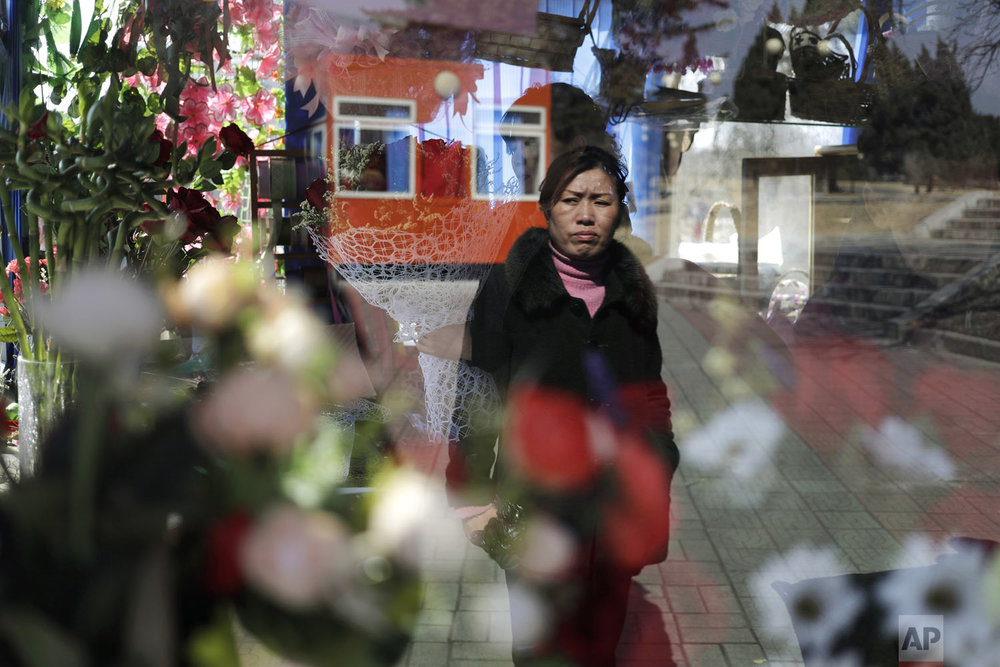 A woman's reflection is seen on the window of a kiosk that sells flowers in celebration of International Women's Day in Pyongyang, North Korea, Friday, March 8, 2019. (AP Photo/Dita Alangkara)