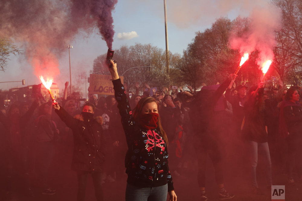 Women hold flares during a march for International Women's Day in Madrid, Spain, Friday, March 8, 2019. Marches and protests are held Friday across the globe to mark International Women's Day under the slogan #BalanceforBetter, with calls for a more gender-balanced world. The day, sponsored by the United Nations since 1975, celebrates women's achievements and aims to further their rights. Thousands of women walked off the job in Spain, joining millions more around the world demanding equality amid a persistent salary gap, violence and widespread inequality. (AP Photo/Bernat Armangue)