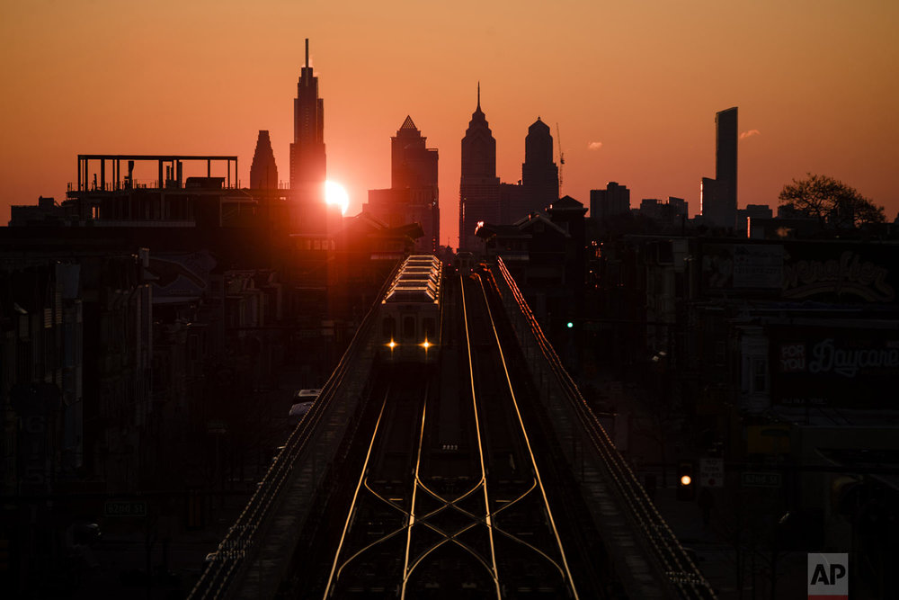 A train heads west as the sun rises from behind the city skyline in Philadelphia, Wednesday, March 6, 2019. The Southeastern Pennsylvania Transportation Authority said members of the Fraternal Order of Transit Police Lodge 109 walked off the job Wednesday. (AP Photo/Matt Rourke)