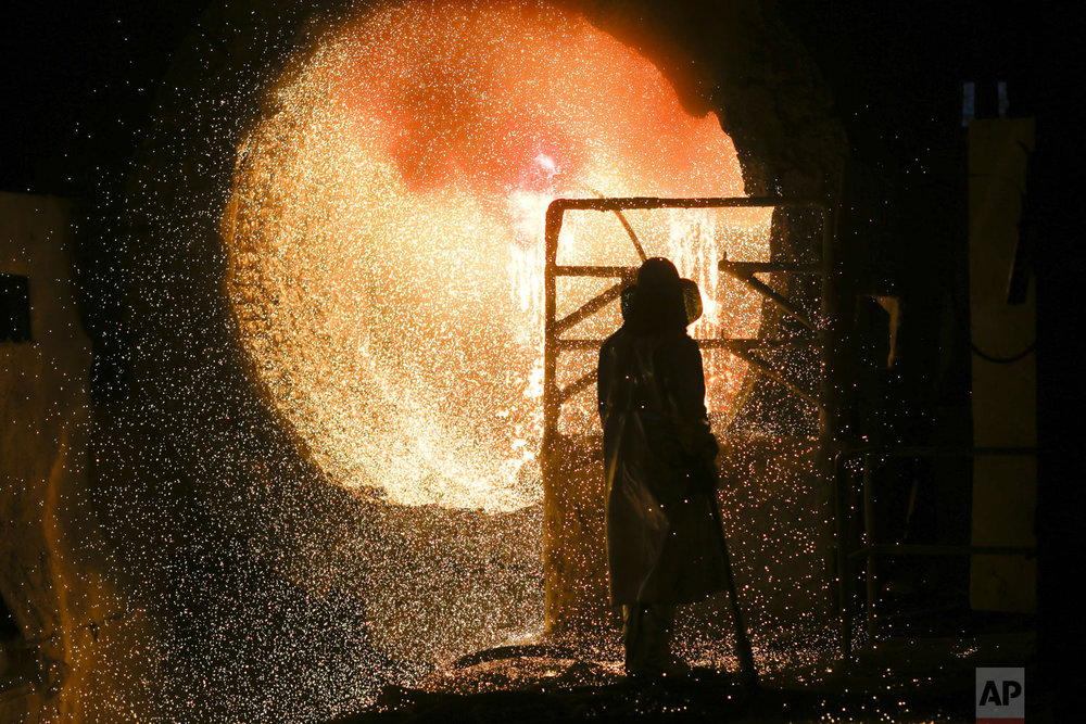 An employee in protective clothing works with a steel pouring ladle during a guided media tour at the steel producer Salzgitter AG in Salzgitter, Tuesday, March 5, 2019. (AP Photo/Markus Schreiber)