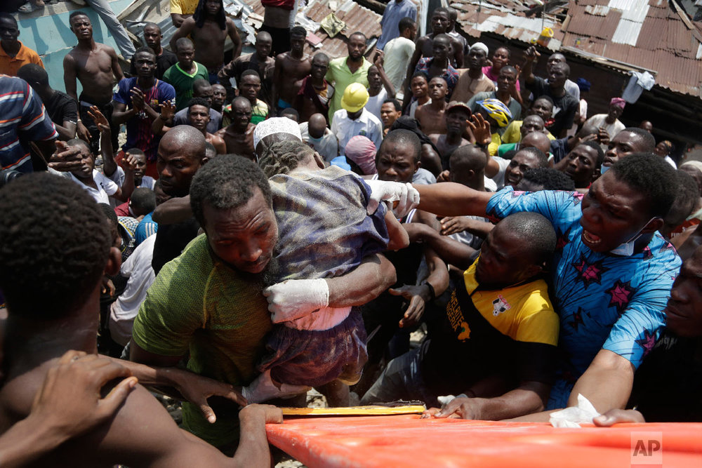 A child is rescued from the rubble of a collapsed building in Lagos, Nigeria, Wednesday, March 13, 2019. (AP Photo/Sunday Alamba)