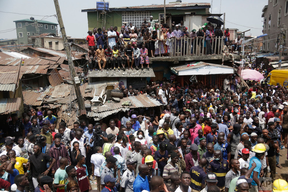 People gather at the scene of a collapsed building in Lagos, Nigeria, Wednesday, March 13, 2019. (AP Photo/Sunday Alamba)