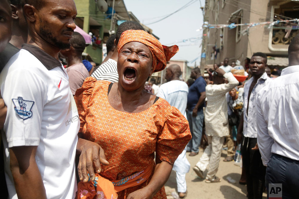 A woman cries as a body of child is recovered from the rubble of a collapsed building in Lagos, Nigeria, Wednesday, March 13, 2019. (AP Photo/Sunday Alamba)