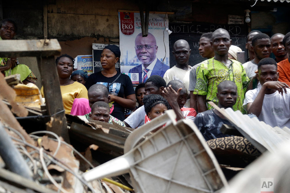 Onlookers stand at the scene of a collapsed building in Lagos, Nigeria, Thursday, March 14, 2019. (AP Photo/Sunday Alamba)