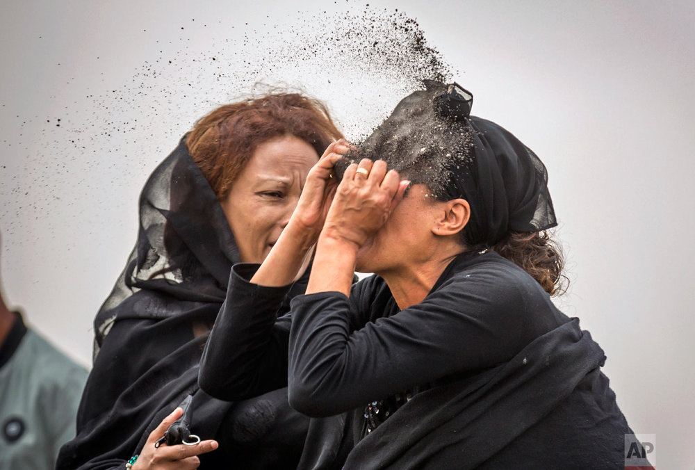 An Ethiopian relative of a crash victim throws dirt in her own face after realizing that there is nothing physical left of her loved one near Bishoftu, Ethiopia on March 14, 2019. (AP Photo/Mulugeta Ayene)