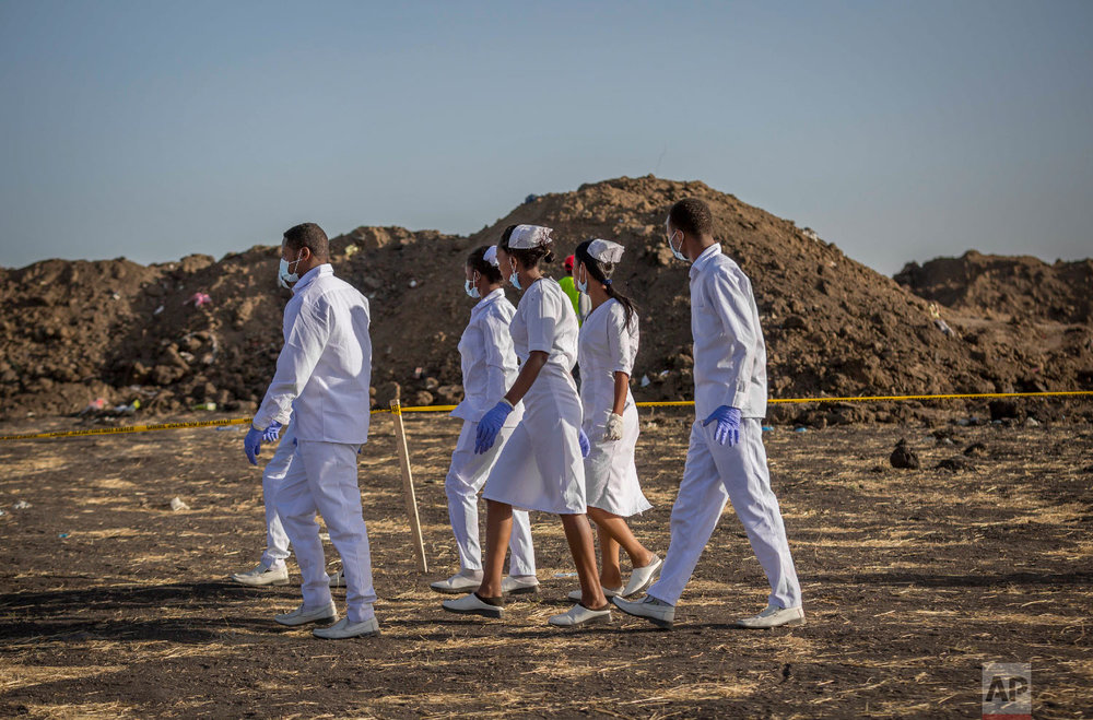 Nurses walk to collect materials, under the instruction of investigators March 12, 2019. (AP Photo/Mulugeta Ayene)