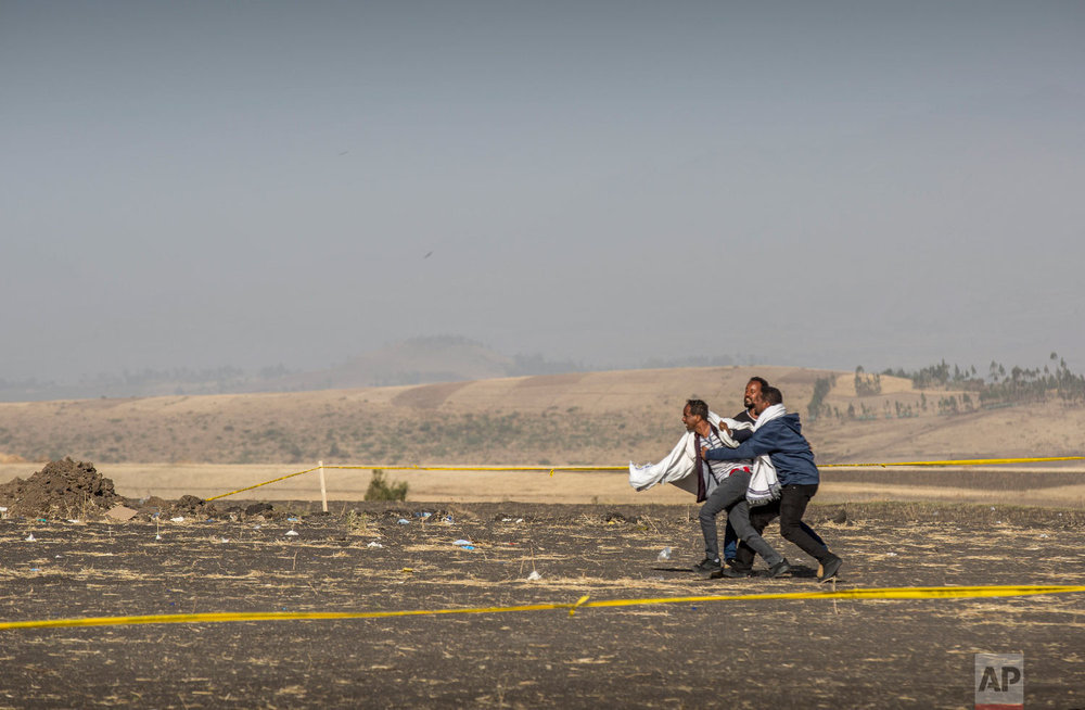 A grieving relative is held back by others at the scene where the Ethiopian Airlines Boeing 737 Max 8 crashed shortly after takeoff on Sunday near Bishoftu, Ethiopia, March 13, 2019. (AP Photo/Mulugeta Ayene)